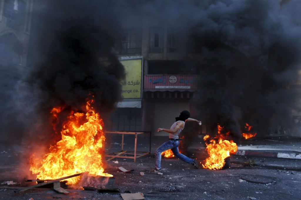Image: Palestinian protester hurl stones at Israeli troops during clashes in the West Bank city of Hebron