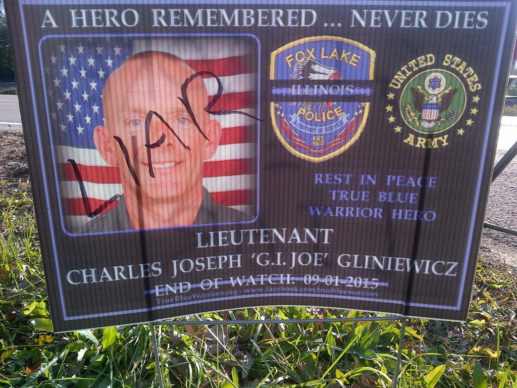 "Image: Someone wrote ""liar"" on a poster honoring Lt. Joseph Gliniewicz."