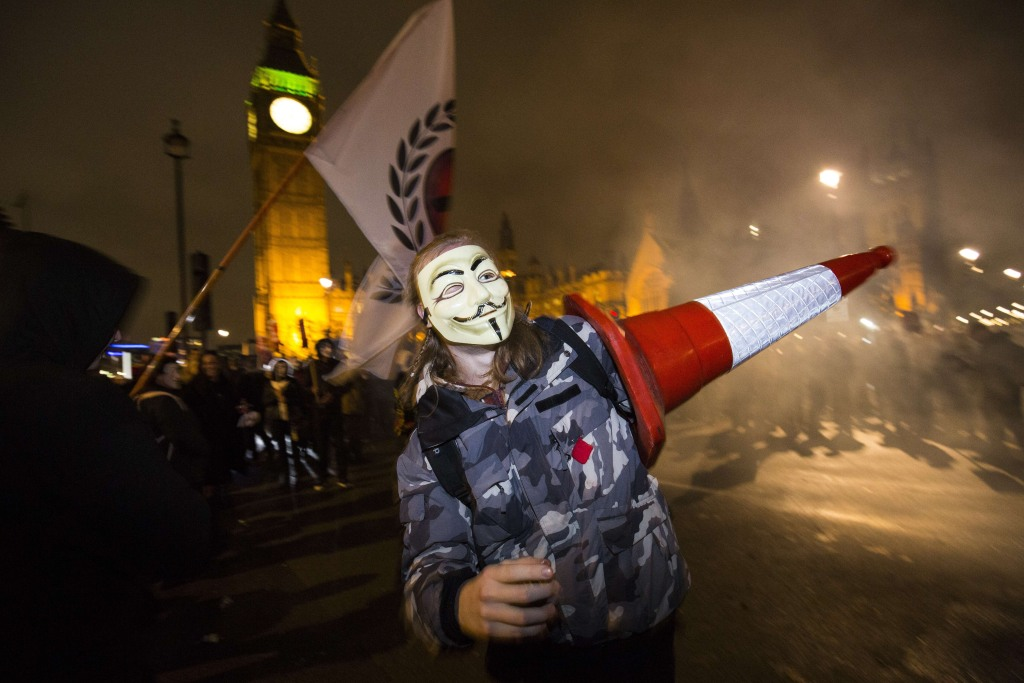 """Image: An anti-capitalist protester wearing a Guy Fawkes mask carries a traffic cone during the """"Million Masks March"""""""