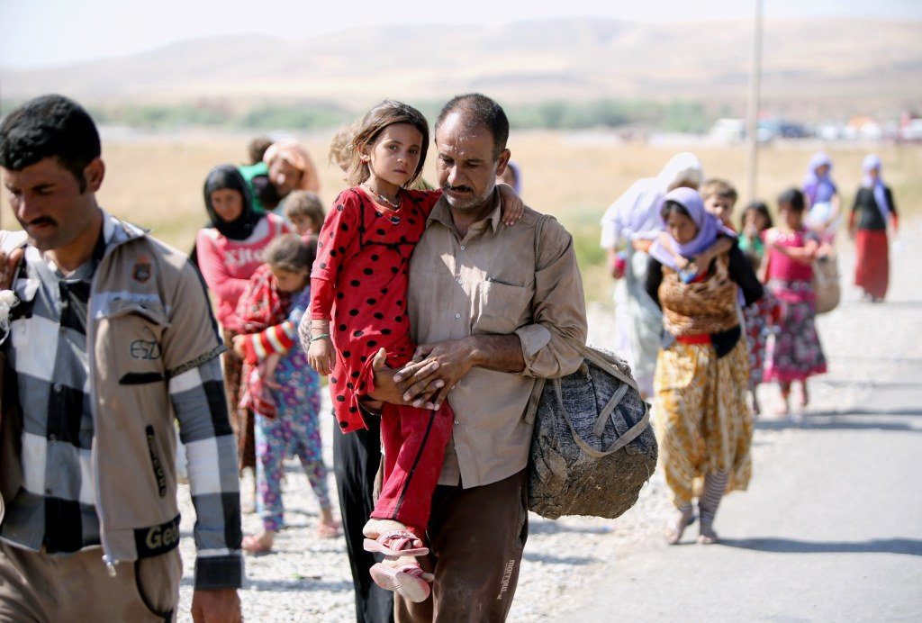 Image: A Yazidi man carries his daughter
