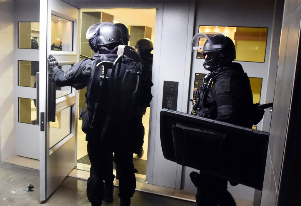 Image: Anti terrorism police officers enter a building during a raid