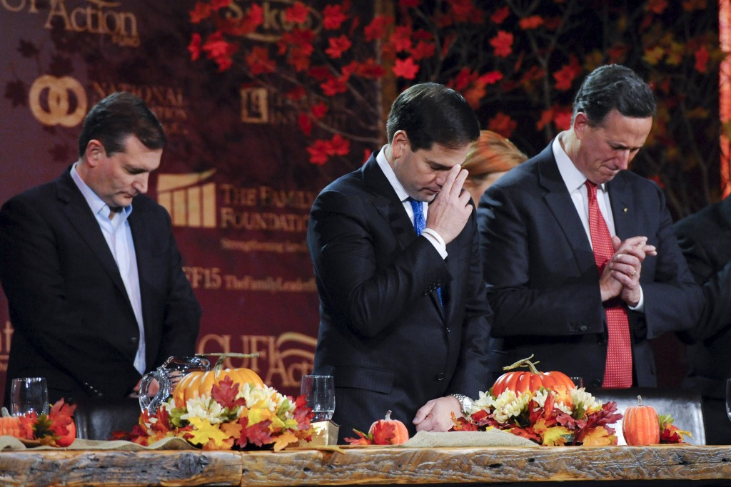 Image: Republican U.S. presidential candidates Cruz, Rubio, and Santorum pray at the Presidential Family Forum in Des Moines, Iowa