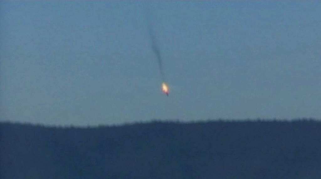 Image: Still image from video showing a war plane crashing in flames in a mountainous area in northern Syria after it was shot down by Turkish fighter jets near the Turkish-Syrian border