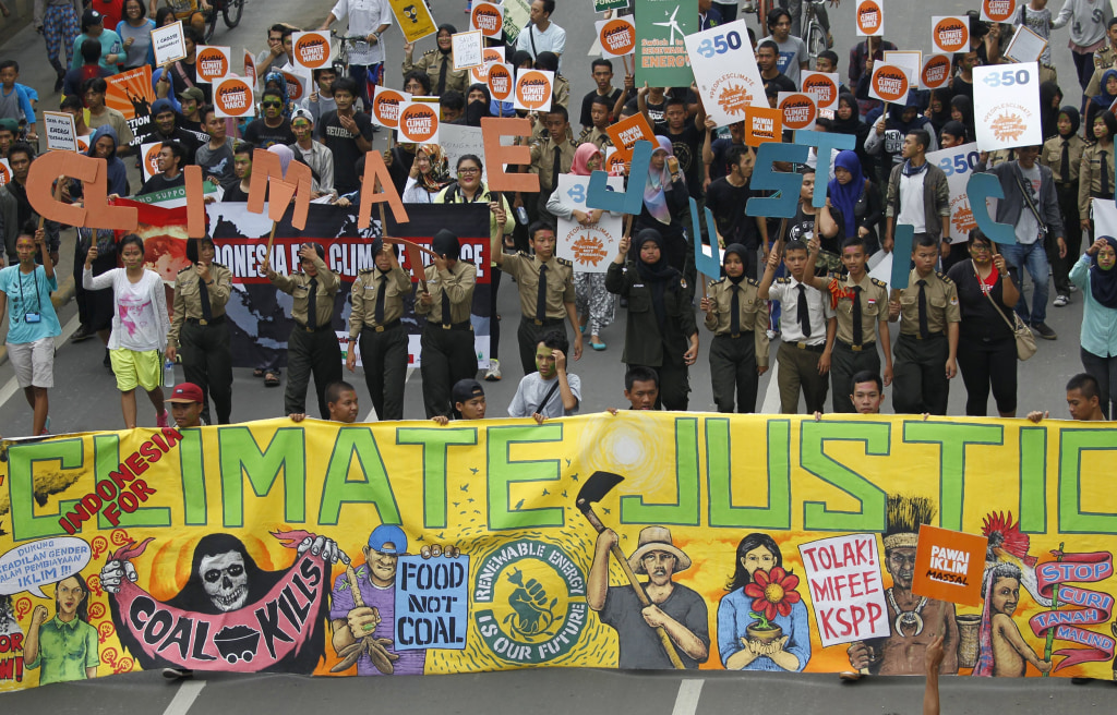 Image: People hold placards and banners as they participate in a march ahead of the Paris World Climate Change Conference in Jakarta
