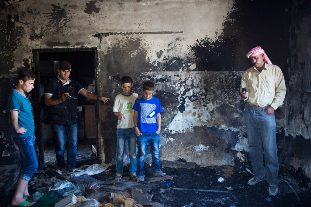 Image: Relatives of slain 18-month-old Ali Dawabsheh stand in the remains of the family's house