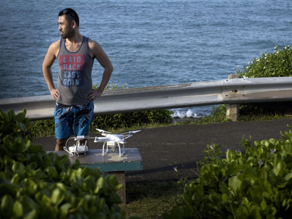Image: A man with a drone stands and watches as a motorcade with U.S. President Barack Obama passes