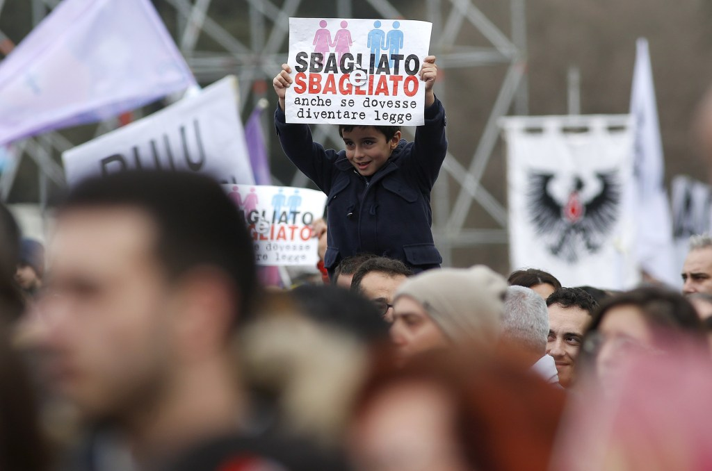 """Image: A child holds a sign reading """"It is wrong even if it becomes law"""" during a rally against same-sex unions and gay adoption in Rome"""