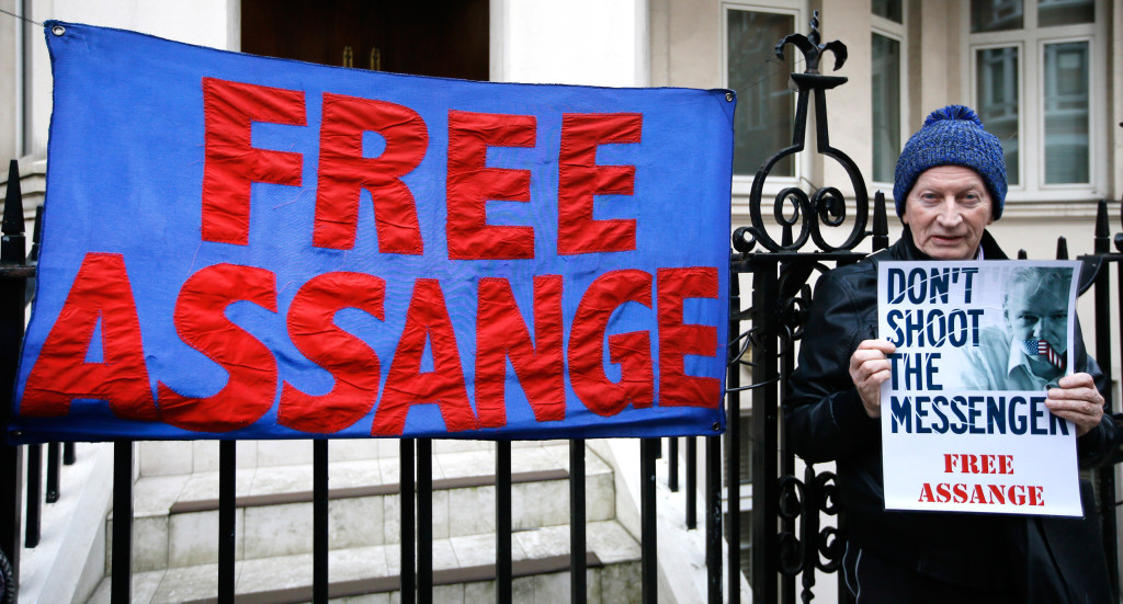 Image: A demonstrator holds a banner outside the Ecuadorean Embassy  in London