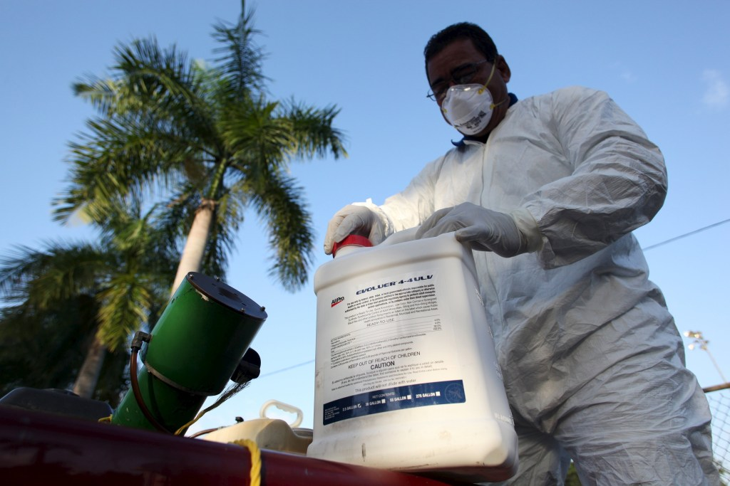 Image: A health worker prepares insecticide before fumigating in a neighborhood in San Juan.