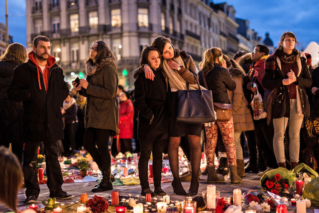 Image: People gather at a memorial site for the victims of attacks in Brussels