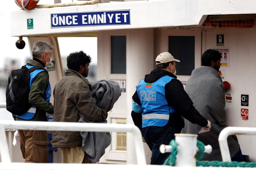 Image: A migrant is escorted onto the ferry on Friday