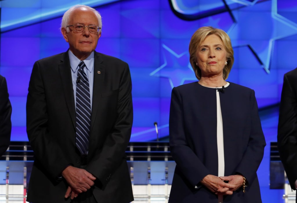 Image: Democratic presidential candidate Senator Bernie Sanders and former Secretary of State Hillary Clinton stand together before the start of the first official Democratic candidates debate of the 2016 presidential campaign in Las Vegas