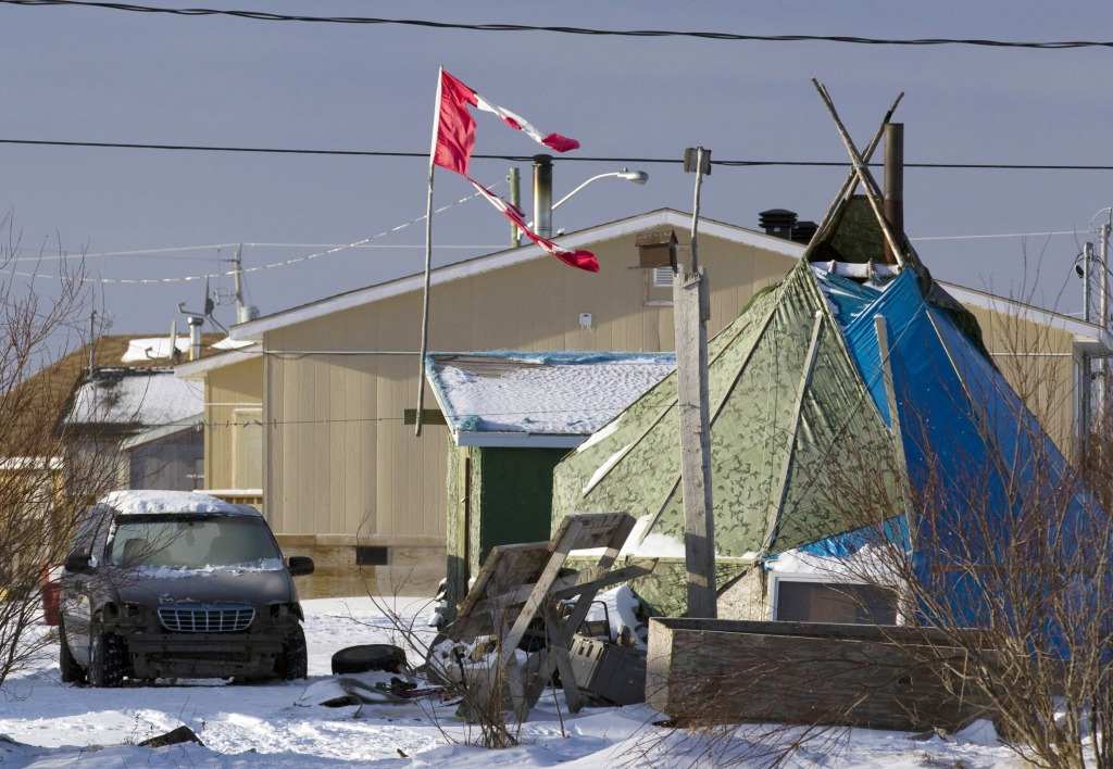 Image: File photo of a tattered Canadian flag flying over a teepee in Attawapiskat Ontario