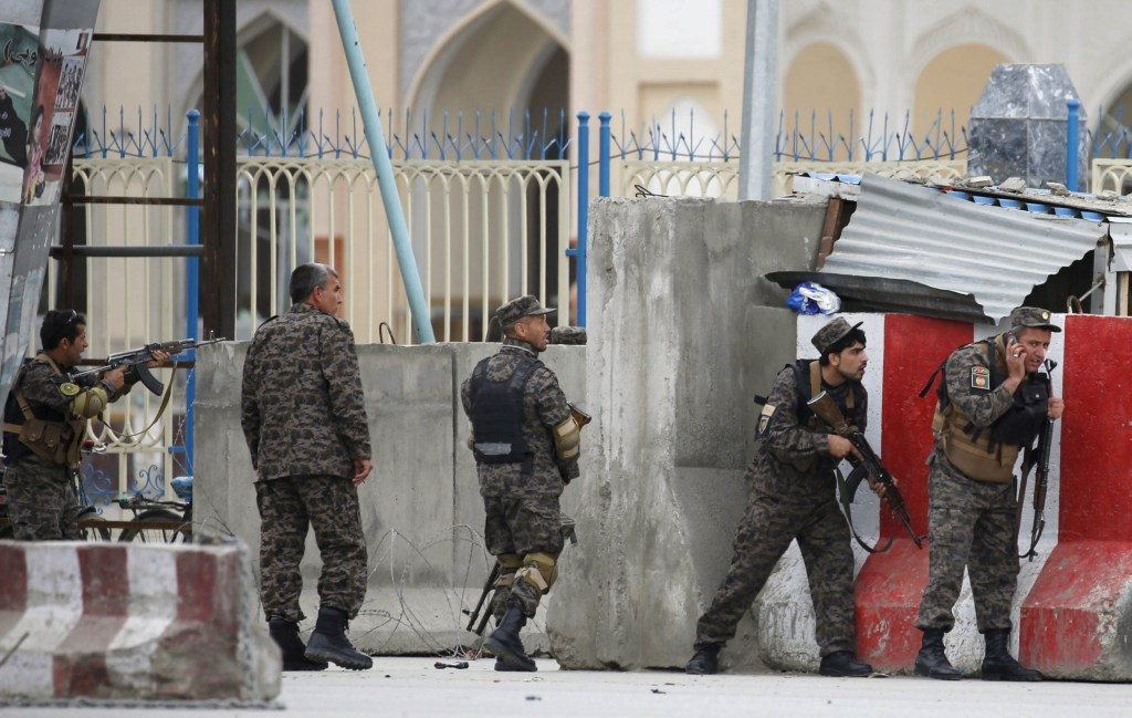 Image: Afghan security forces take position at the site of a suicide car bomb attack in Kabul