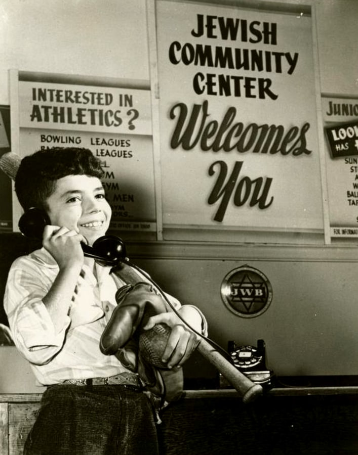 A Jewish Community Center promotional photo, circa 1950, shows a young boy carrying baseball equipment.