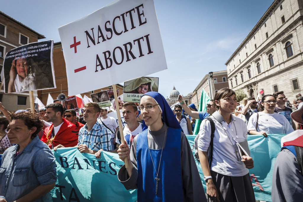 """Image: A nun holds a placard reading """"More Births Minus Abortions"""""""
