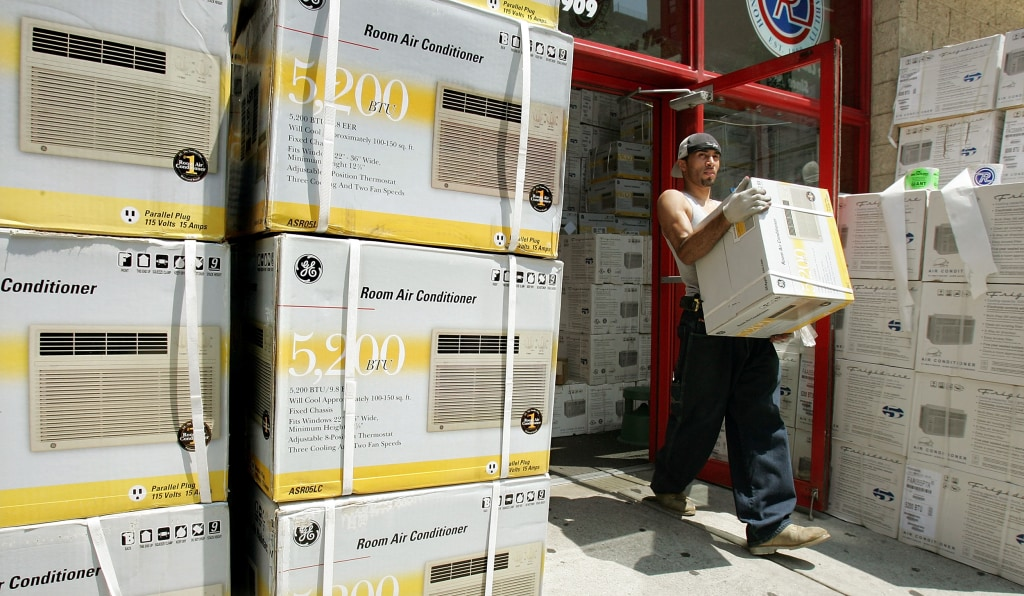 Image: A worker carries a new air conditioner out of a PC Richard store