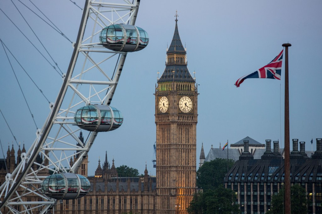 Image: A Union flag flies beside the London Eye in front of the Big Ben and The Houses of Parliament