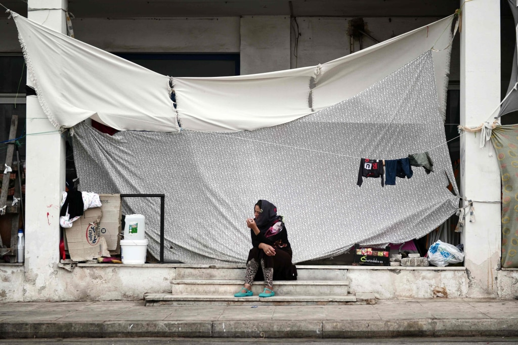 Image: A woman sits next to the makeshift tents at the unofficial camp for migrants in Athens