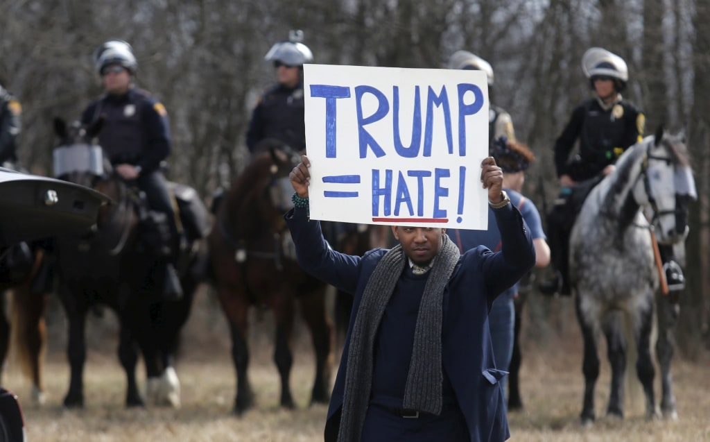 Image: An anti-Trump protester holds his protest sign in front of mounted police outside a rally for Republican U.S. presidential candidate Donald Trump in Cleveland