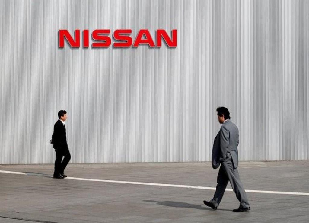 Men walk past a Nissan Motor Co logo at the company's global headquarters in Yokohama