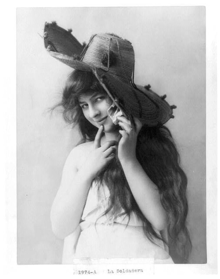 La Soldadera -- Young woman, half lgth., wearing large hat, with right hand raised to chin.
