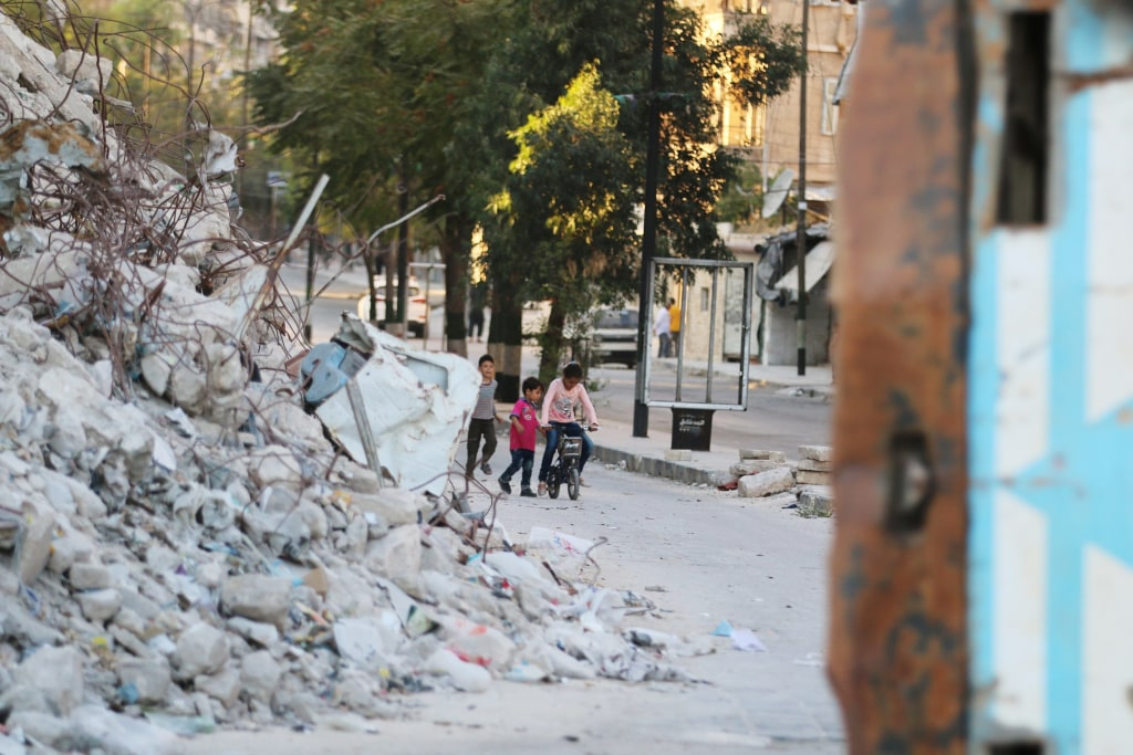 Image: Children play with a bicycle in Aleppo's rebel-held Bab al-Hadid neighborhood