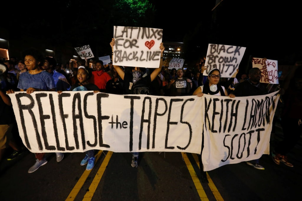 Image: Protesters hold signs while marching to demonstrate against the police shooting of Keith Scott in Charlotte
