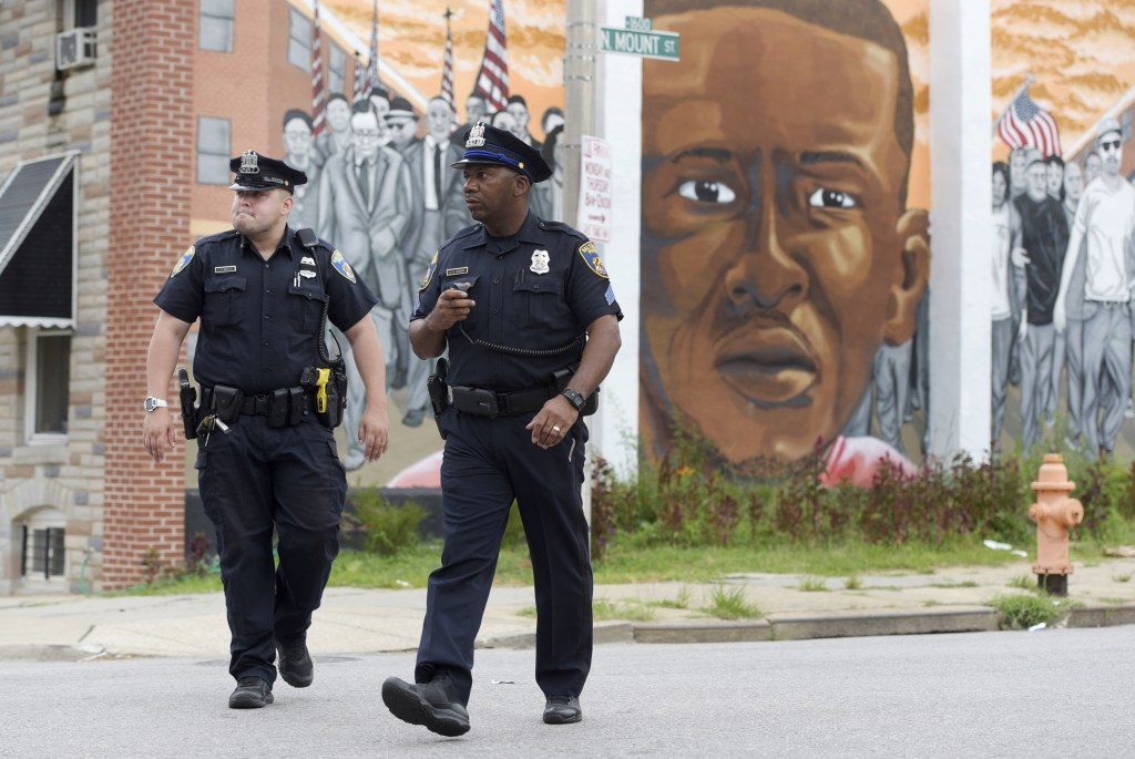 Image: Baltimore police walk near a mural depicting Freddie Gray