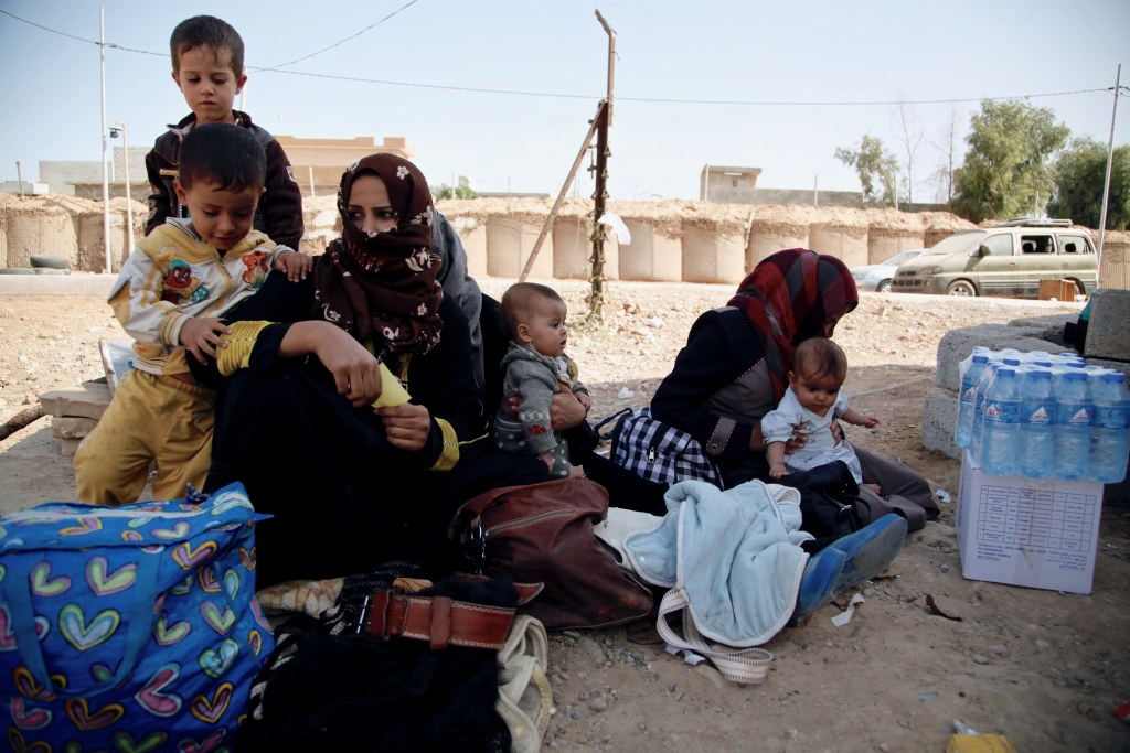 Image: A group of mothers sit with their children at Dibis checkpoint