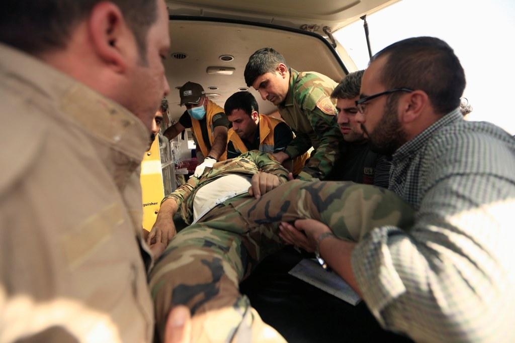 Image: Kurdish Peshmerga fighters carry their injured comrade