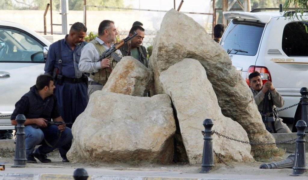 Image: Peshmerga forces stand behind rocks in Kirkuk