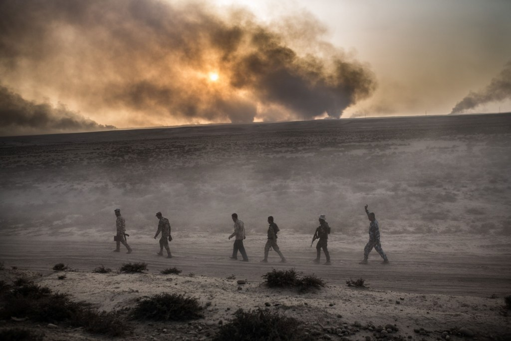 Image: Iraqi soldiers walk on a road as smoke billows from the Qayyarah area