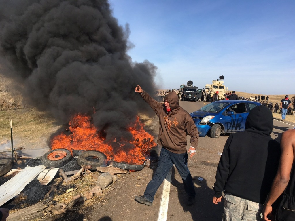 Image: Demonstrators stand next to burning tires as armed soldiers and law enforcement officers assemble
