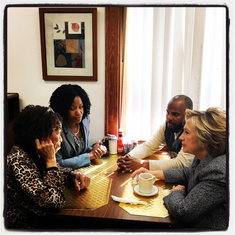 Image: Democratic presidential candidate Hillary Clinton has coffee with patrons at Cozy Spot