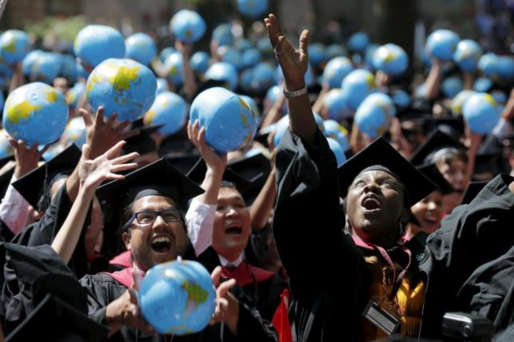 Olufunke Michaels and her classmates celebrate after receiving their degrees from the John F. Kennedy School of Government during the 364th Commencement Exercises at Harvard University in Cambridge