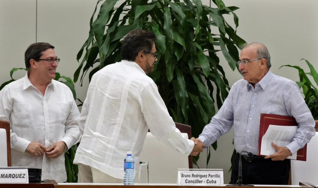 Image: Colombia's FARC lead negotiator Ivan Marquez and Colombia's lead government negotiator Humberto de la Calle shake hands while Cuba's Foreign Minister Bruno Rodriguez looks on, after signing a new peace deal
