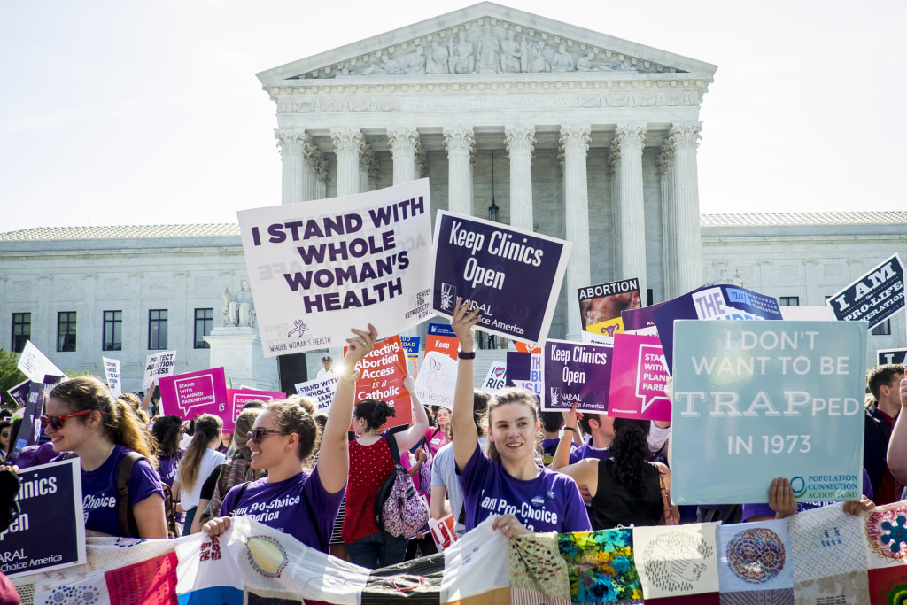 Image: Pro-choice and pro-life activists demonstrate on the steps of the  Supreme Court