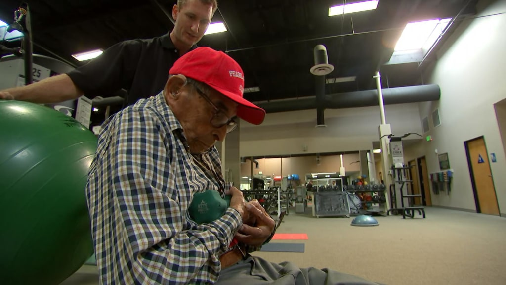 Pearl Harbor survivor Ray Chavez working out with his trainer