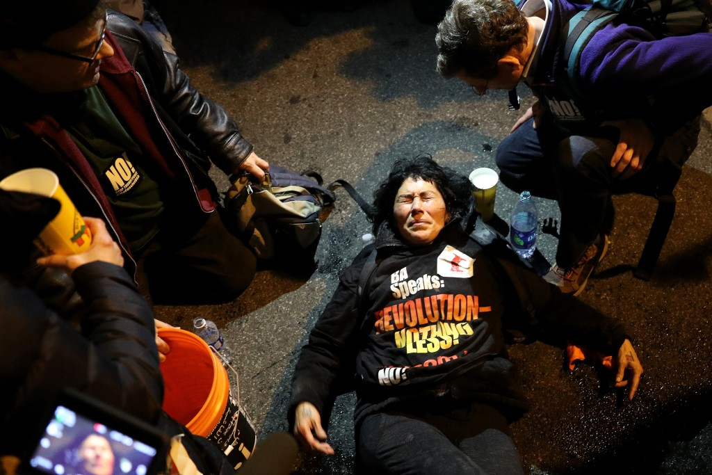 Image: A protester has her eyes doused with water after being pepper sprayed by police outside of the DeploraBall at the National Press Building on Jan. 19, 2017 in Washington, D.C.