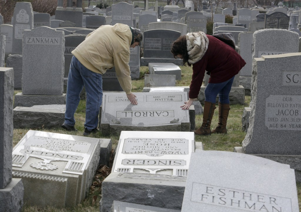 Image: Joe Nicoletti and Ronni Newton of the Taconey Holmesburg town watch group pay their respects at a damaged headstone in Mount Carmel cemetery, Feb. 27, 2017, in Philadelphia.