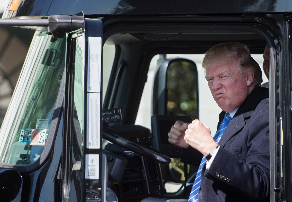 Image: Trump sits in the drivers seat of a semi-truck as he welcomes truckers and CEOs to the White House