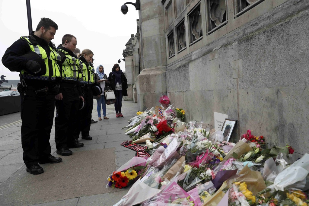 Image: Police officers and civilians look at flowers left near Westminster Bridge in London