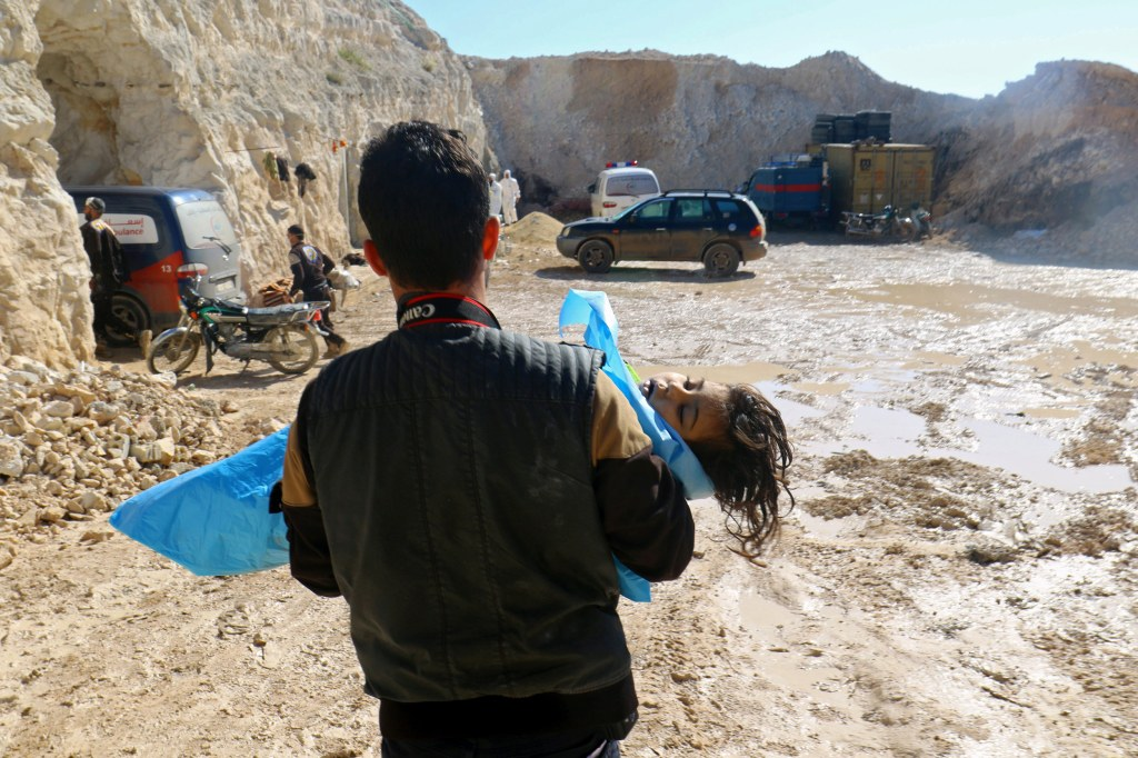 Image: A man carries the body of a dead child, after what rescue workers described as a suspected gas attack in the town of Khan Sheikhoun in rebel-held Idlib