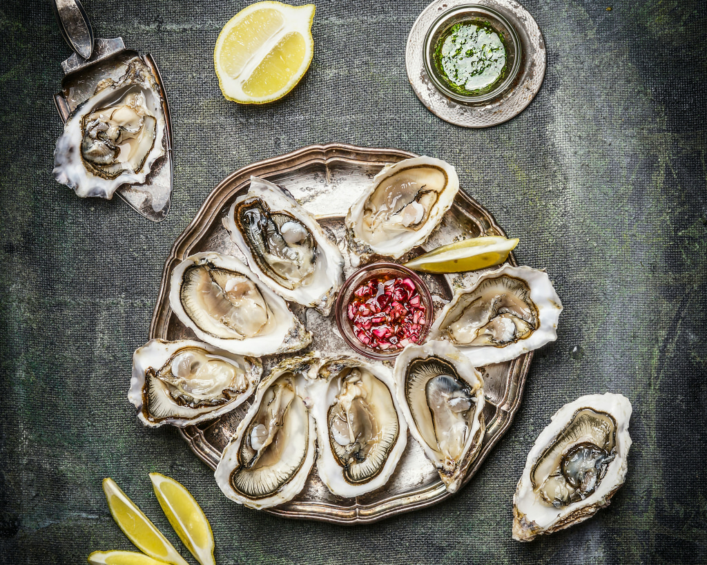 Oysters plate with lemon and sauces , top view