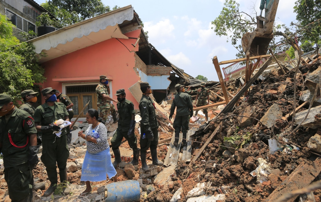 Image: Sri Lankan army rescuers remove debris from a buried house
