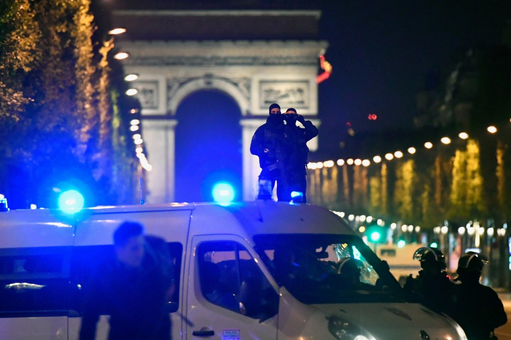 Image: Police look through binoculars  as officers secure the area after a gunman opened fire on the Champs Elysees