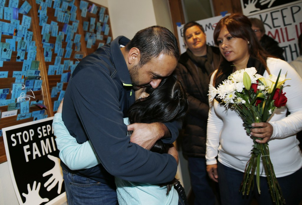 Image: Arturo Hernandez, left, hugs his 9-year-old daughter, Andrea, with his wife, Ana Sauzameda standing next to them