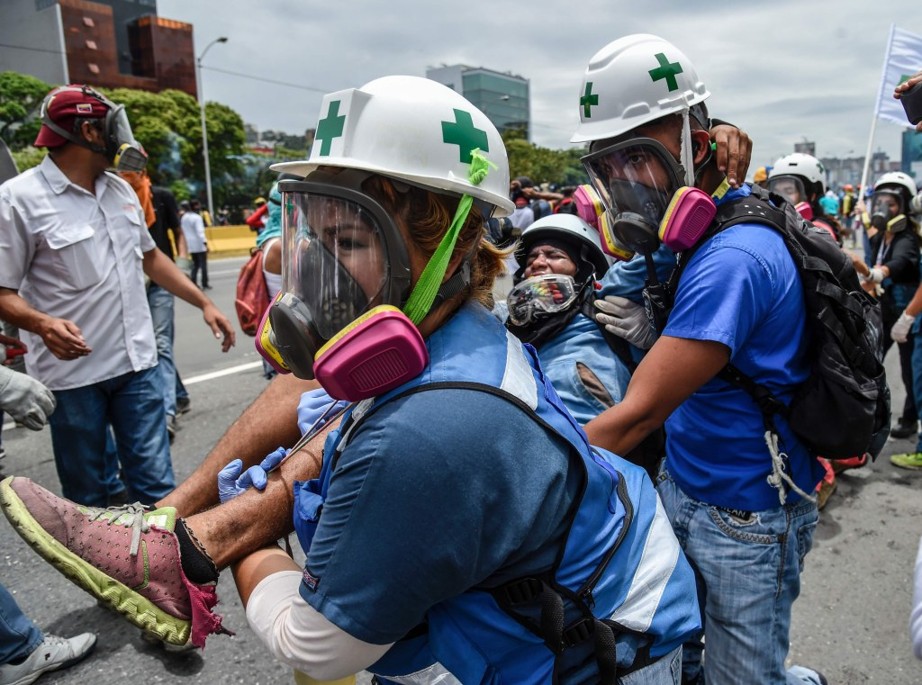 Image: An opposition demonstrator wounded during clashes with riot police in Venezuelan