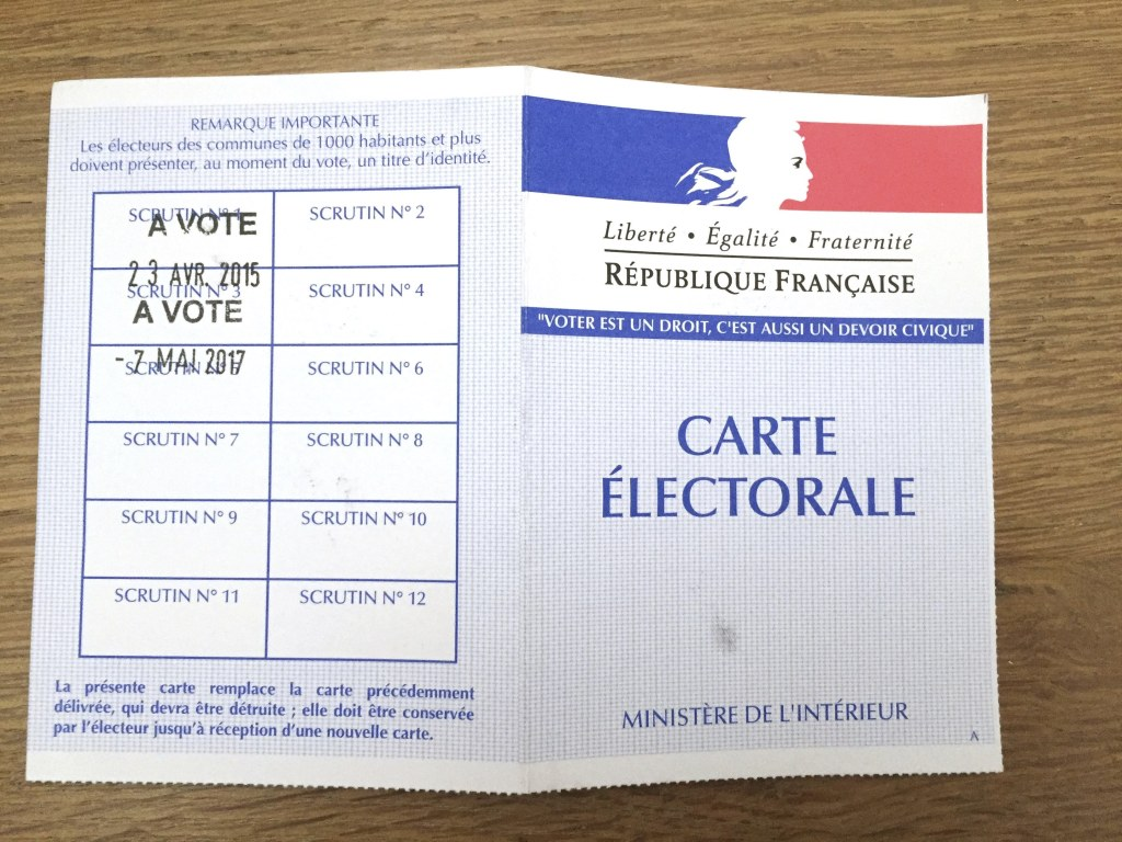 Image: A voter registration card pictured as voters prepare to vote for the second round of the French presidential election